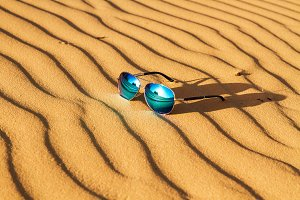 Sunglasses on the sand in the desert.