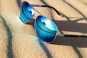 Sunglasses on the sand in the desert.