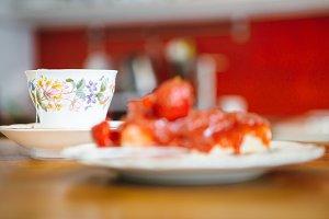 Cup of tea near unfocused cake
