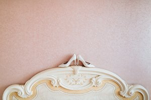 Ivory wedding women's shoes stand on bedhead close to wall.