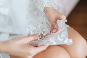 Beautiful legs. Bride's cute knees is. Sitting on bed. Closeup.