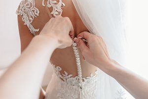 Bride's dress being buttoning. First-person view.