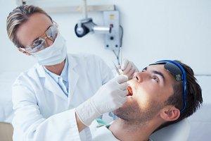 Female dentist examining mans teeth