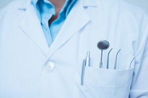 Mid section of dental tools in dentists pocket