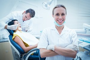 Smiling female dentist with assistant examining womans teeth