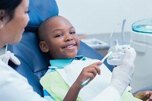 Dentist teaching happy boy how to brush teeth