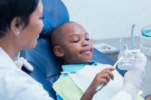 Female dentist teaching boy how to brush teeth