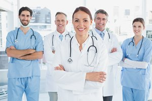 Smiling doctor with fellow doctors