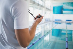 Swimming instructor holding stopwatch by the pool
