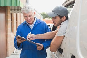 Delivery driver showing customer where to sign