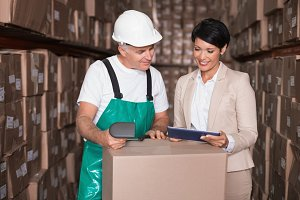 Warehouse worker scanning box with manager holding tablet pc