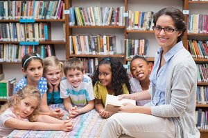 Cute pupils and teacher reading in library