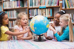 Cute pupils looking at globe in library
