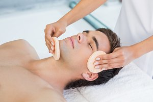 Man receiving facial massage at spa center