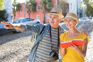Happy tourist couple using guide book in the city