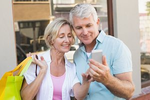 Happy mature couple looking at smartphone together