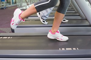 Low section of a couple running on treadmills at gym