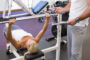 Trainer with clipboard besides woman lifting barbell in gym