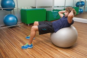 Man doing abdominal crunches on fitness ball in gym