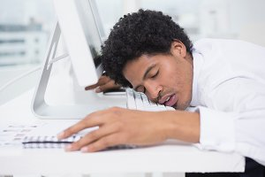 Handsome photo editor sleeping at desk