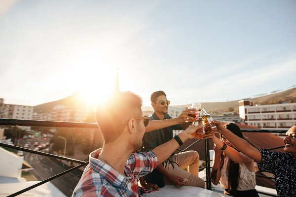 Friends toasting drinks at rooftop