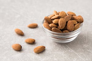 Almond in the glass bowl on stone table.