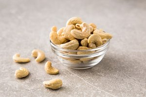 Cashew nuts in the glass bowl on stone table