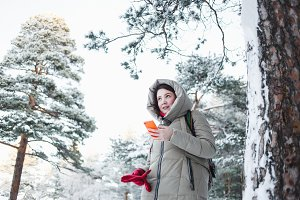 Cheerful woman texting on orange smartphone during a trip to the forest in winter. Brunette model wearing warm jacket with hood, red gloves