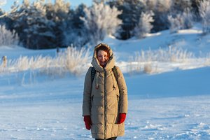Young cheerful woman walking at the winter cold sunny day on the background of trees and snow. Girl dressed in warm beige jacket  red gloves