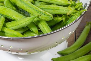 Pea pods in a white colander