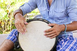 man playing on djembe