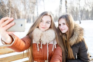Two smiling girls make selfie in winter park