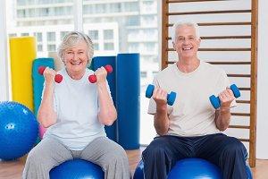 Happy senior couple lifting dumbbells on exercise ball