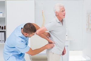 Physiotherapist giving back massage to senior man