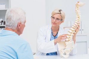 Doctor explaning anatomical spine to male patient