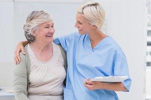 Happy nurse with arm around senior patient in clinic