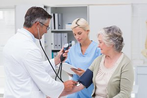 Doctor checking patients blood pressure while nurse noting it