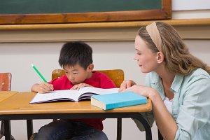 Teacher helping pupil in classroom
