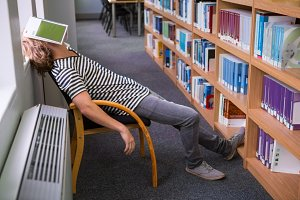 Student asleep in the library with book on his face