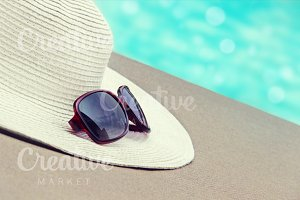 Straw hat, glasses by the pool