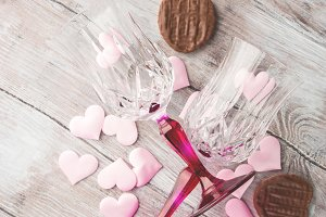 Two stemmed glasses with hearts and chocolate