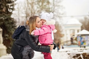 Mother and daughter hugging. Winter
