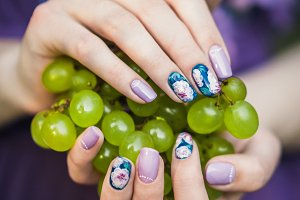 Hands with Nails Holding Grapes