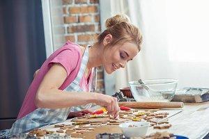 Teenage girl icing cookies