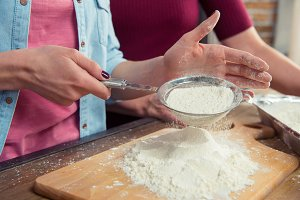 Woman sifting flour on cutting board
