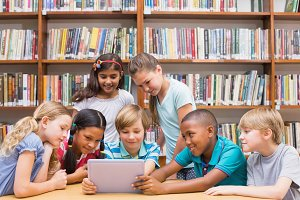 Cute pupils using tablet computer in library