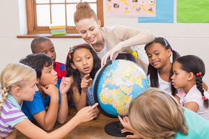 Cute pupils and teacher in classroom with globe