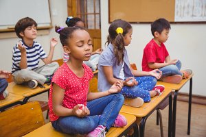 Pupils meditating in lotus position on desk in classroom