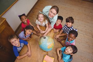 Cute pupils smiling around a globe in classroom with teacher