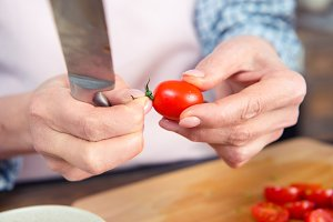 Woman holding knife and tomato